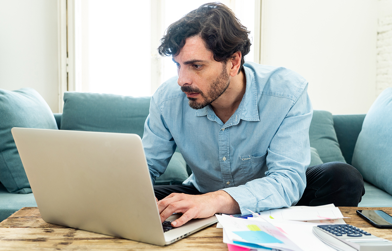 A man wearing a smart shirt sits at his coffee table working on his laptop