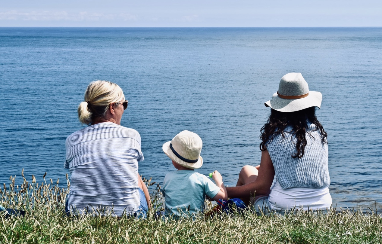 Two woman and a child sit on a grassy bank in front of the sea