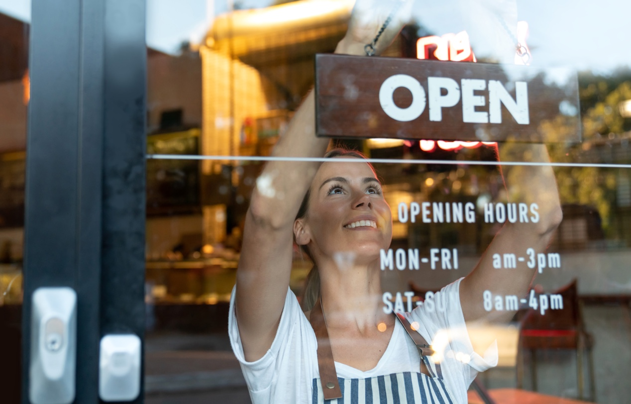 "A woman turns the sign of a cafe to read ""open"""