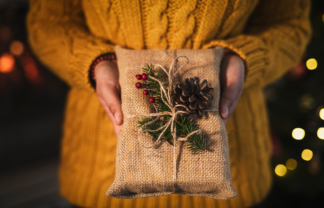 A lady holding a rustic looking wrapped christmas present out in front of her