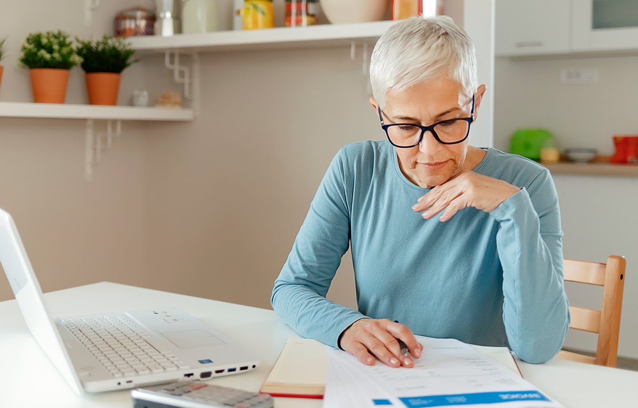 An older woman sits at her modern looking workplace reading a document