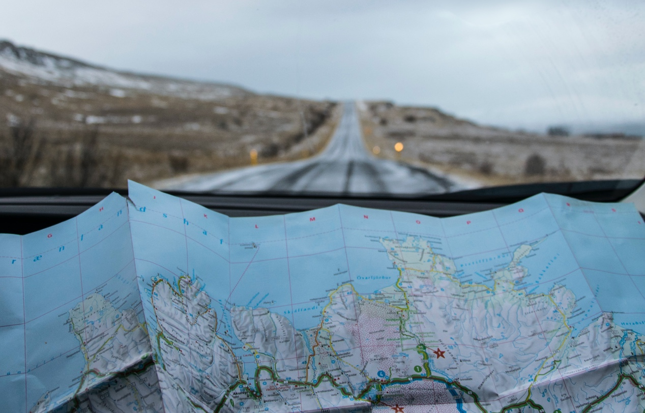 A map is in the foreground of a long road