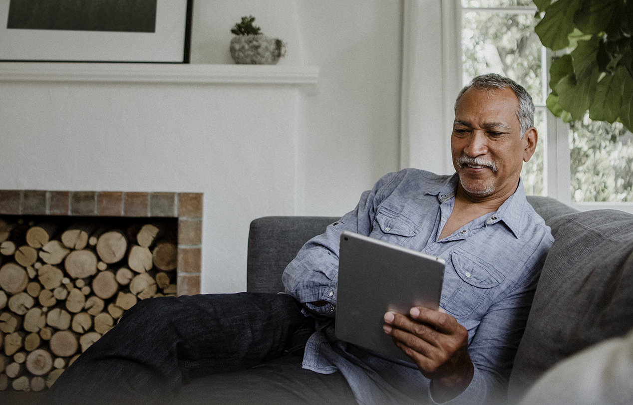 A middle aged man sits on his sofa using his iPad