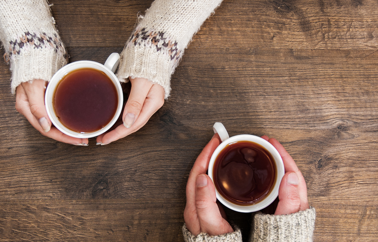 2 people warming their hands on a mug of coffee
