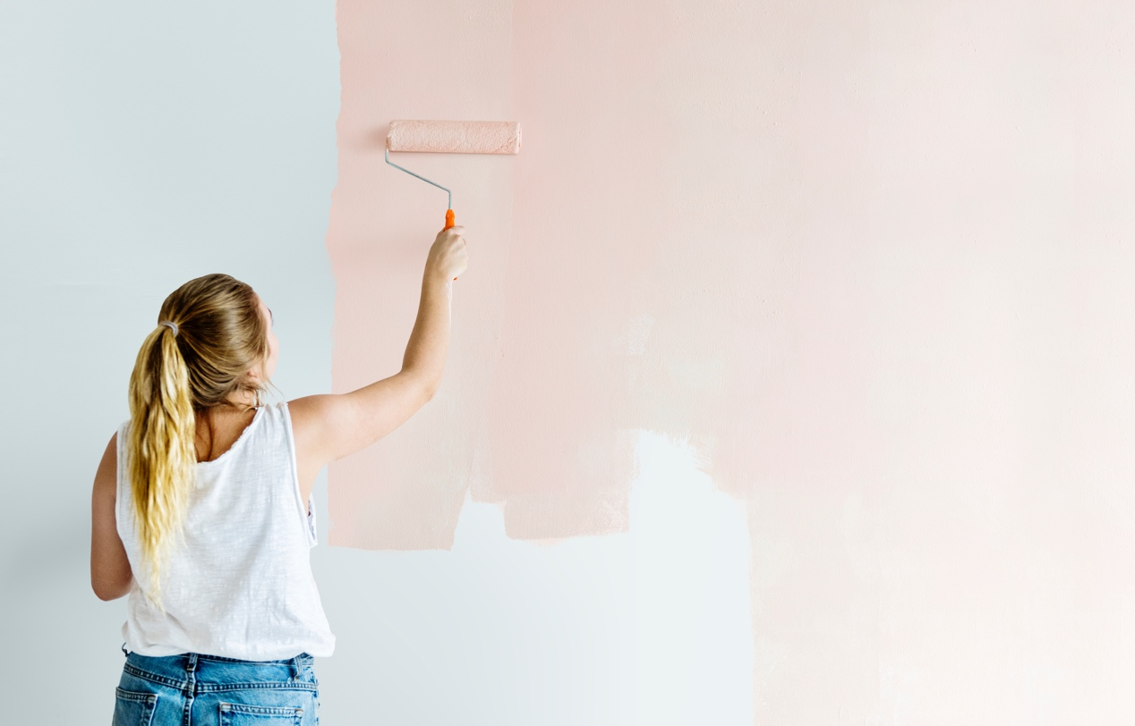 A girl paints a wall in her house