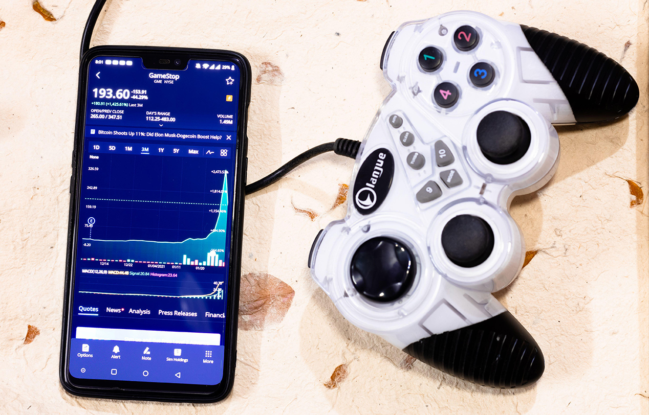 Gamer control and a mobile screen showing the share prices for GameStop